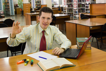 Young cheerful student or teacher in library shows ok gesture.