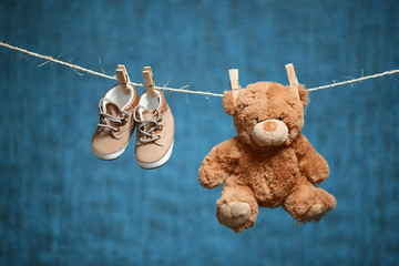 brown toy bear and baby shoes hanging on a rope on a blue background