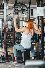 Woman training her back and shoulder with in a gym