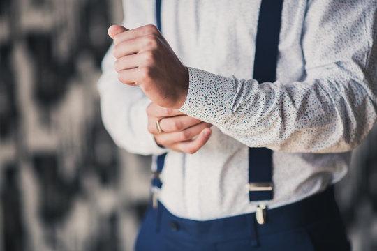 a man adjusting his cufflinks