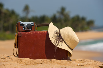 Travel  vintage suitcase and camera on a beach
