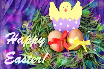 easter hand made decorated greeting card: yellow eggs and hand made hatched chicken in eggshell in green grass twigs nest on purple background with inscription happy easter