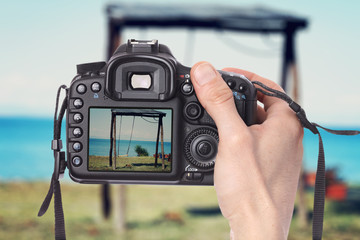 Male hand taking photo of a wooden swing on the beach with digital DSLR camera.