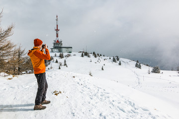 Mountaineer standing at the top of the Uršlja gora mountain photographing with his mobile phone