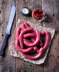 Raw sausages from beef meat on an old wooden background.