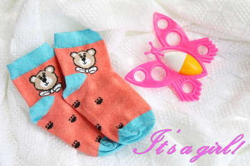 greeting card: red knitwear newborn baby socks with bears and colorful pink butterfly rattle on crocheted blanket white background with inscription it's a girl