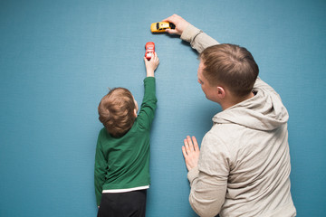 Father and son are playing with toy cars in the home. Cheerful time together at home.