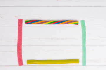 Colorful licorice and chewy candies on wooden white board