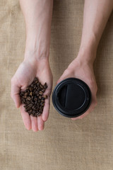 Coffee to go cup on burlap background in man hands