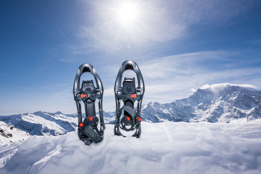Snowshoeing against snowcapped mountains in a sunny day