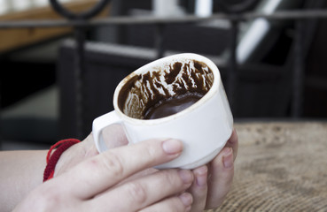 Women's  hands hold cap of turkish coffee, looking fall, fortune