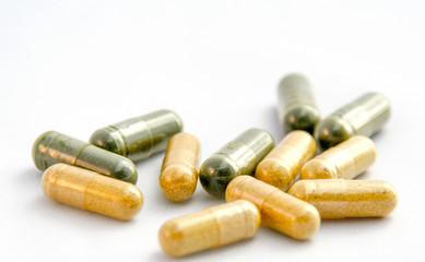 Żółte i zielone tabletki na białym tle