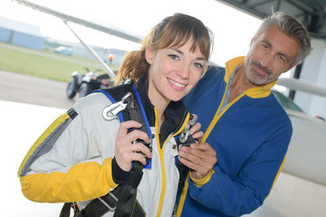 Portrait of woman being prepared for parachute jump