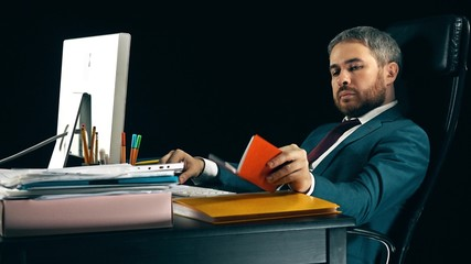 Handsome bearded businessman working on his computer and using his planner. Black background