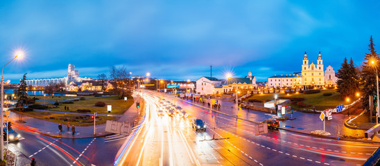 Minsk, Belarus. Night Traffic On Illuminated Street And Cathedral