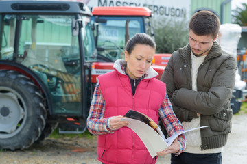 saleswoman convincing young famrer to buy new agricultural machinery Wall mural