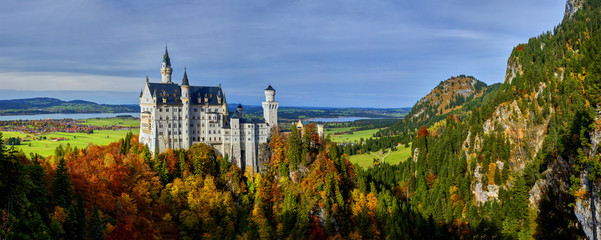 Neuschwanstein Castle with colorful sky and autumn trees. Bavaria, Germany.
