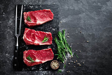 Photo sur cadre textile Viande Raw meat, beef steak on black background, top view