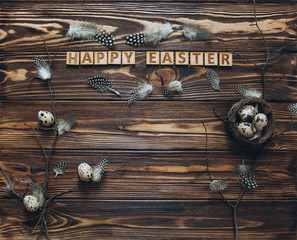 Decoration with quail eggs, nest and feathers. Vintage wooden background with sample text Happy Easter.