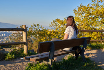 Mujer joven sentada en un banco en la naturaleza