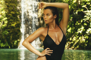 Woman wearing black swimsuit in the jungle oasis