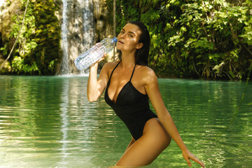 Woman with a bottle of water in the jungle oasis