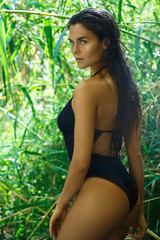 Woman wearing black swimsuit in the jungle
