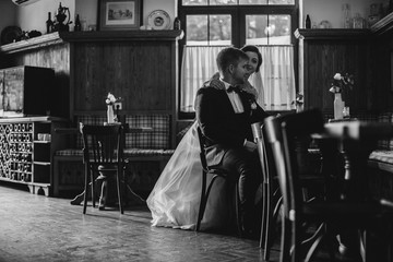 Cute married couple in cafe, bride kissing a groom . Pure tenderness