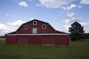 Large, beautiful red barn on bright green grass, surrounded by cloudy blue sky
