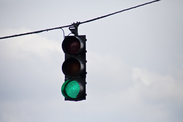 Green traffic light surrounded by overcast sky.