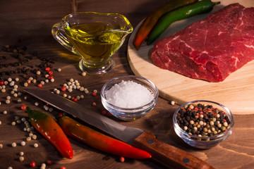 Сырой  стейк из говядины с перцем чили и специями на деревянном фоне