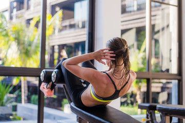 portrait of an athletic woman doing exercising abdominals work-out lying in gym at luxury hotel at summer
