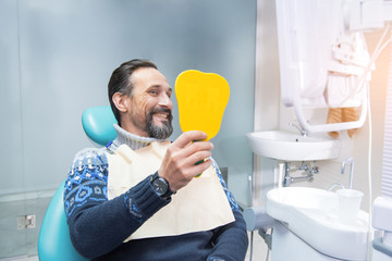Man in a dental chair. Person smiling and holding mirror. Make your smile perfect.