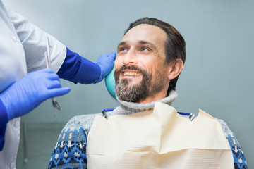 Smiling man at the dentist. Happy mature male. Advice from stomatologist.