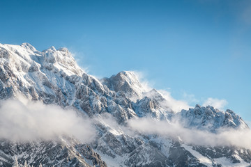 Snowcapped rocky mountain landscape with blue sky