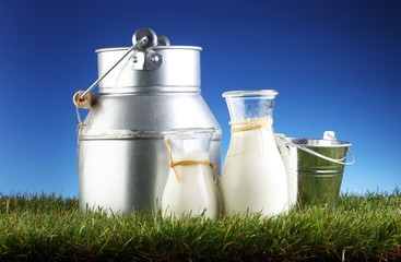 Milk jug and glass on the grass. On a background of the sunny sky.