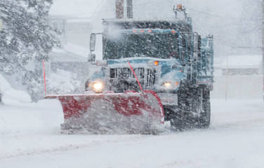 Snow plow with a red plow working in a blizzard