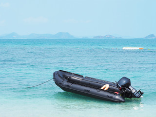 Empty black inflatable boat in the sea