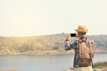 Tuinposter Happy Asian hipster man backpack in nature background, Relax time on holiday concept travel , color of vintage tone and soft focus