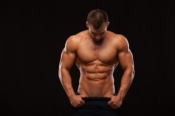 Strong Athletic Man - Fitness Model showing Torso with six pack abs. stands straight and puts his hands in trousers. isolated on black background with copyspace