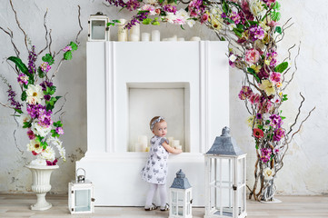 Beautiful baby girl in an elegant dress with flowers studio