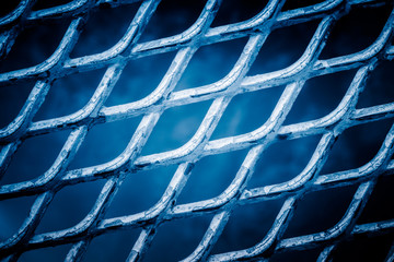 full frame shot of mesh wire fence in blue tone.
