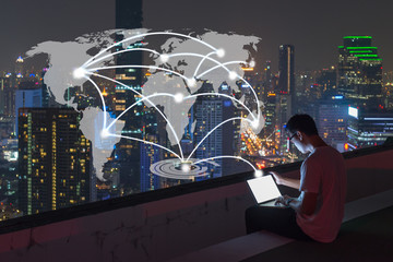 Wall Mural - Male using computer labtop on city rooftop with world connection concept
