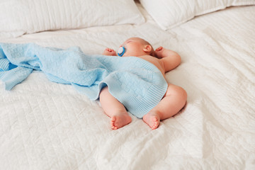 Portrait of a cute adorable white Caucasian baby newborn in diaper, sleeping dreaming with pacifier soother in mouth, lying on bed, covered with blue blanket