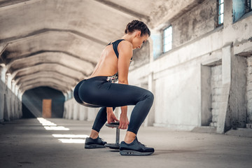Full body portrait of the sporty female doing squats.