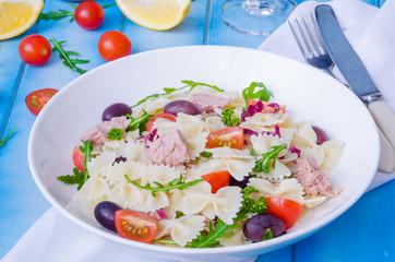 Pasta salad with tuna, olives, cherry tomatoes and arugula