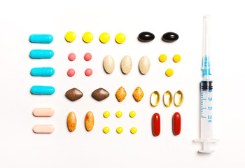 multi-colored tablets and prick, vitamins, dietary supplements in a row