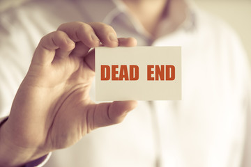 Businessman holding DEAD END message card