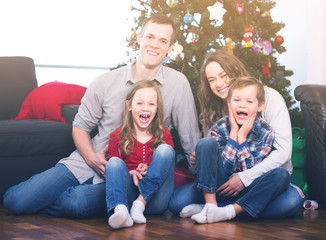 Parents with children preparing for photo with Christmas tree