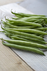Bunch of fresh green beans on the wooden background